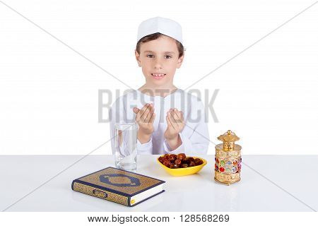 Young Muslim boy praying while waiting breaking fast in Ramadan - sitting on a table with water dates Quran and Ramadan lantern