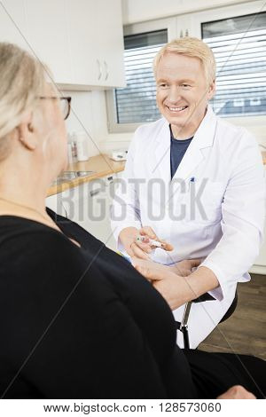Smiling Physician Collecting Senior Patient's Blood For Test In  poster