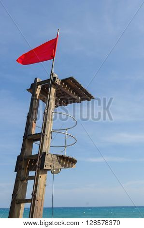 View on lifeguard post with warning red flag against of blue sky