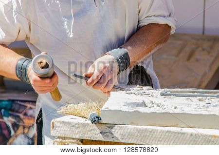 Faceless man working with chisel. Sculpting on stone