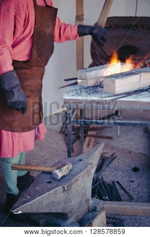 farrier working with with a hammer and an anvil in the forge