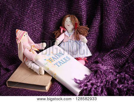 Rag dolls with fairy tales books on bedspread. Childhood concept