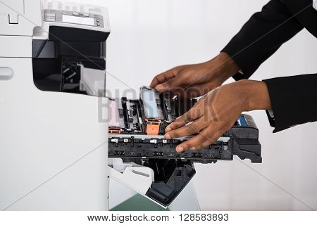 Close-up Of African Businesswoman Hand Fixing Photocopy Machine In Office