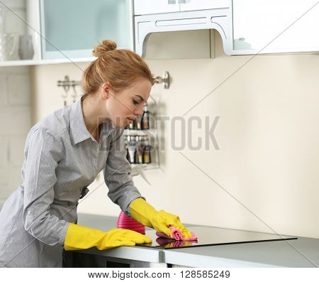 Young woman cleaning a electric stove with a rag and cleanser