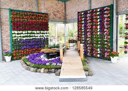 Lisse, Netherlands - April 4, 2016: Pavillion interior view with boat and flowers in dutch spring garden Keukenhof, Lisse, Netherlands