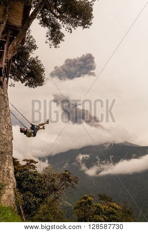 Banos De Agua Santa - 08 March 2016: Silhouette Of A Happy Young Teenager Boy Swinging On A Swing Above The Andes Mountains Tungurahua Volcano Explosion March 2016 In The Background South America In Banos De Agua Santa On March 08 2016