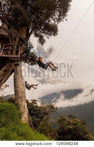 Banos De Agua Santa - 08 March 2016: Silhouette Of Two Young Men On A Swing In Banos De Agua Santa Tungurahua Volcano Explosion On March 2016 In The Background Ecuador In Banos De Agua Santa On March 08 2016