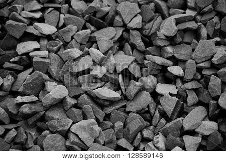 Black and white photo of pile of pebble rocks as background.