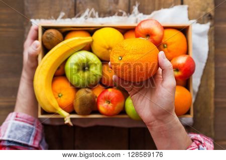 Man in tartan plaid shirt holds a box full of fresh fruits and a big juicy orange. Fruit harvest - apples oranges lemon kiwi banana. Rustic wooden table.