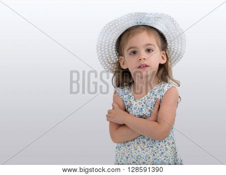 Cute little girl with a flowered dress and a hat join hands on a grey background