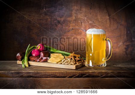 mug of unfiltered beer with sausage, onion, radish, cheese, nuts, toast on cutting board