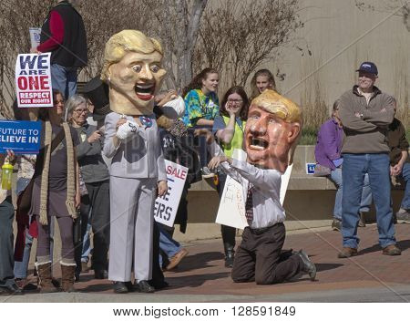 Asheville, North Carolina, USA - February 28, 2016: Humorous effigies of Donald Trump kneeling at Hillary Clinton's feet as she holds onto a bag of money while Bernie Sanders supporters watch holding signs behind them at a Bernie Sanders campaign rally