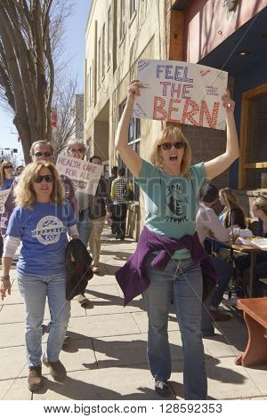 Asheville, North Carolina, USA - February 28, 2016: A crowd of Bernie Sanders rally supporters march holding a variety of signs about isuues like health care during a campaign rally on February 28, 2016 in downtown Asheville NC
