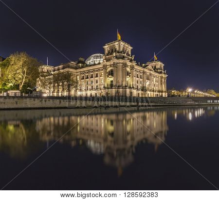 The German Reichstag By Night With Reflection In River Spree