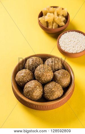 The indian sesame sweet or tilgul laddu or til gul laddu, made up of jaggery and sesame seeds, indian sweet for Makar Sankranti festival, in terracotta bowl with jaggery & raw sesame, isolated on white background