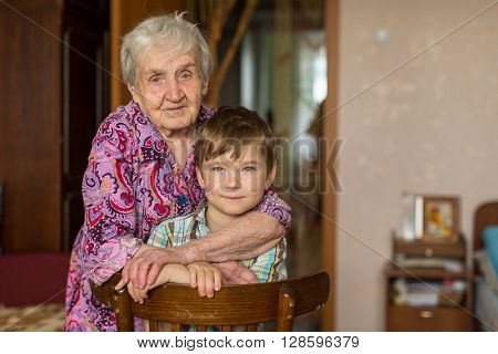 Portrait of grandmother with her grandson in her house.