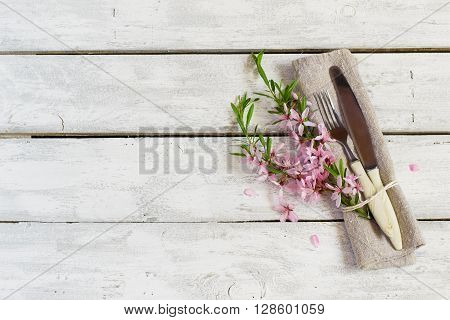 Spring table setting with almond flowers and cutlery holiday background
