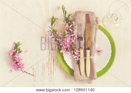 Spring table setting with sprigs of flowering almonds tinted.