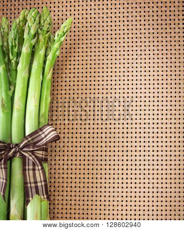 Asparagus bind with brown ribbon on brown wickerwork background
