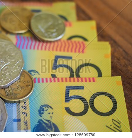 Australian currency, fifity dollar notes and assorted coins, in closeup