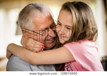 Authentic photo of happy grandfather hugging with his granddaughter indoor at home ** Note: Shallow depth of field