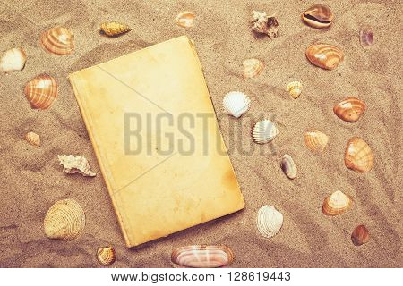 Vintage book and sea shells on sandy beach vacation mood and summer lifestyle objects in flat lay top view arrangement.