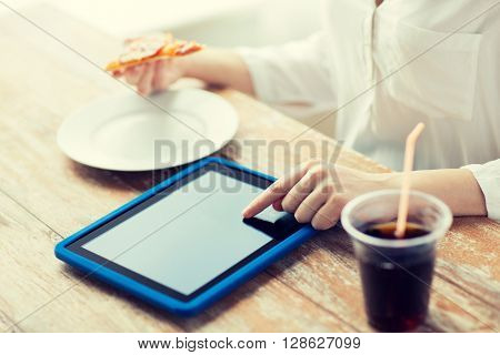 fast food, people, technology and diet concept - close up of woman with tablet pc computer, pizza and cola counting calories at table