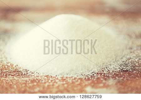 food, junk-food, cooking and unhealthy eating concept - close up of white sugar heap on wooden table