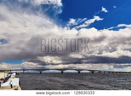 Saratov, Russia - 23 april 2016: The sky with clouds the bridge through Volga and a fragment of the embankment in Saratov. Unrecognizable people
