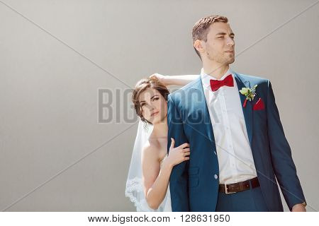 Young wedding couple standing outside against gray background outdoors