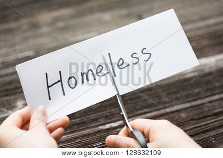 holds card with text homeless on old wood plate