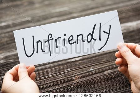 holds card with text unfriendly on old wood plate
