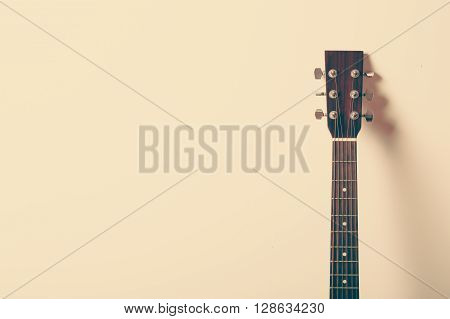 Acoustic guitar headstock on old style background.