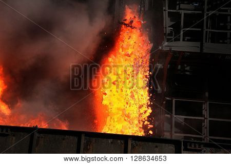 Hot coke being pushed from oven chamber.