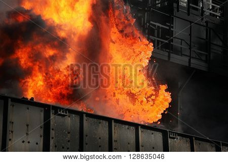 Hot coke being pushed from oven on heavy industrial plant.