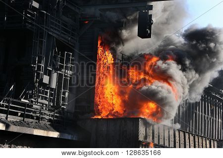 Pushing hot coke from oven in heavy industrial plant.
