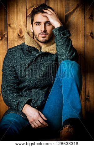 Vogue shot of a handsome male model in jeans and a coat sitting by a wooden wall. Men's beauty, seasonal fashion.