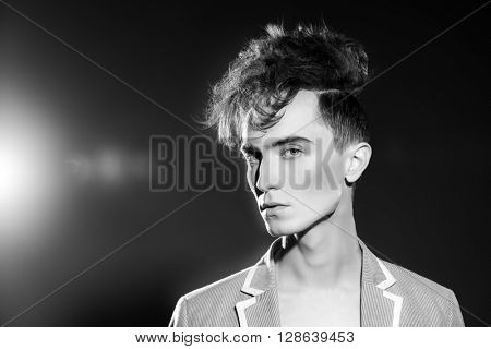Black-and-white portrait of a fashion male model with stylish upright hair. Beauty, fashion.