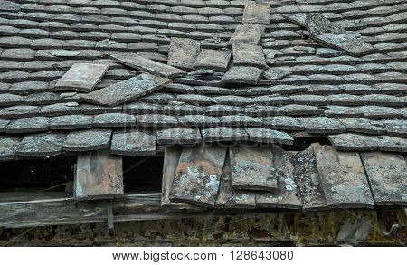 A decrepit old house with a damaged and devastated roof and tiles.