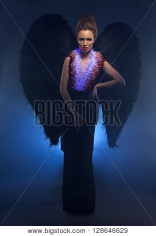 Beautiful female succubus. Concept photo in studio, on dark background