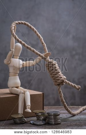 Small Wooden Dummy Sitting With Hangman's Noose And Coins