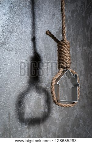Small House Framed With Hangman's Noose Over The Grey Concrete Wall