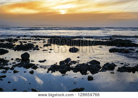 reflections at rocky beach near ballybunion on the wild atlantic way ireland with a beautiful yellow sunset
