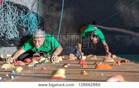 Elderly Female Moving Up on Outdoor Climbing Wall Sporty Clothing on Fitness Training Intense but Positive Face another Climber Start His Ascent on Background