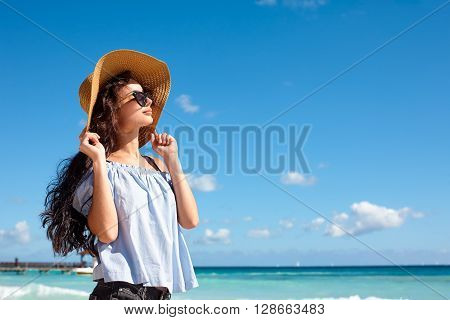 Beach vacation. A beautiful woman in a sunhat and sunglasses standing on beach and looking at the sun