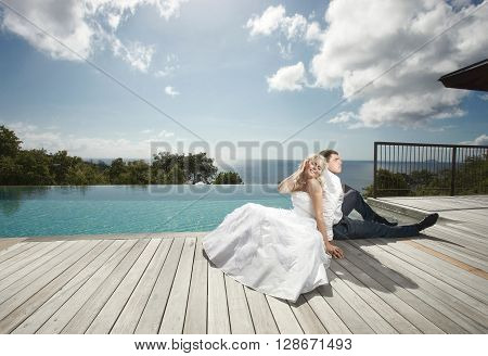 Beautiful Young Couple Lying Close To Pool Before Wedding Under Sunlight.