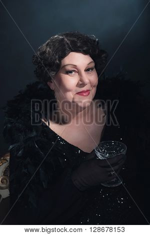 Smiling vintage woman holding champagne glass. 1930s classic portrait.