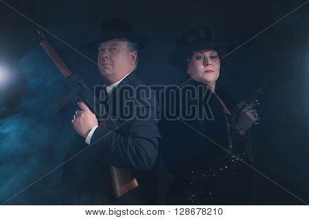 Vintage 1940s gangster couple. Classic studio portrait.