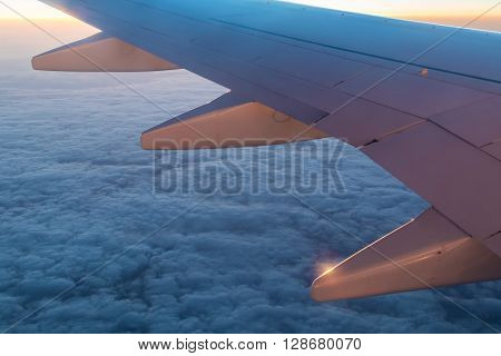 The wing of the airplane above the clouds at sunset closeup