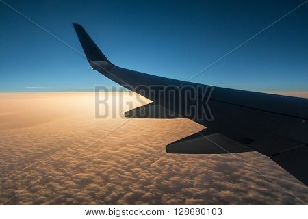 The wing of the airplane above the clouds at sunset